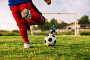 action sport outdoors of a group of kids having fun playing soccer football for exercise in community t20 mRKNKg